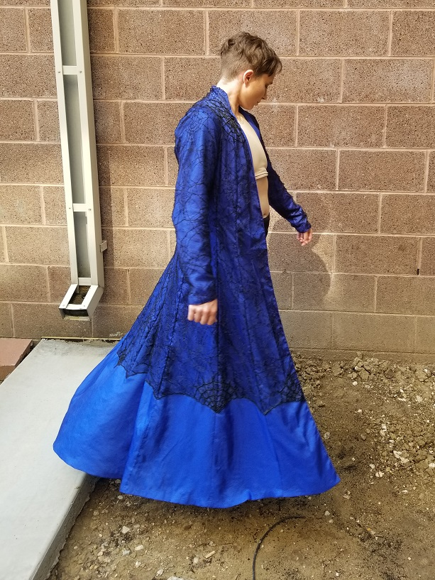 A person cosplaying as Derossi Vargo in a blue beaded coat